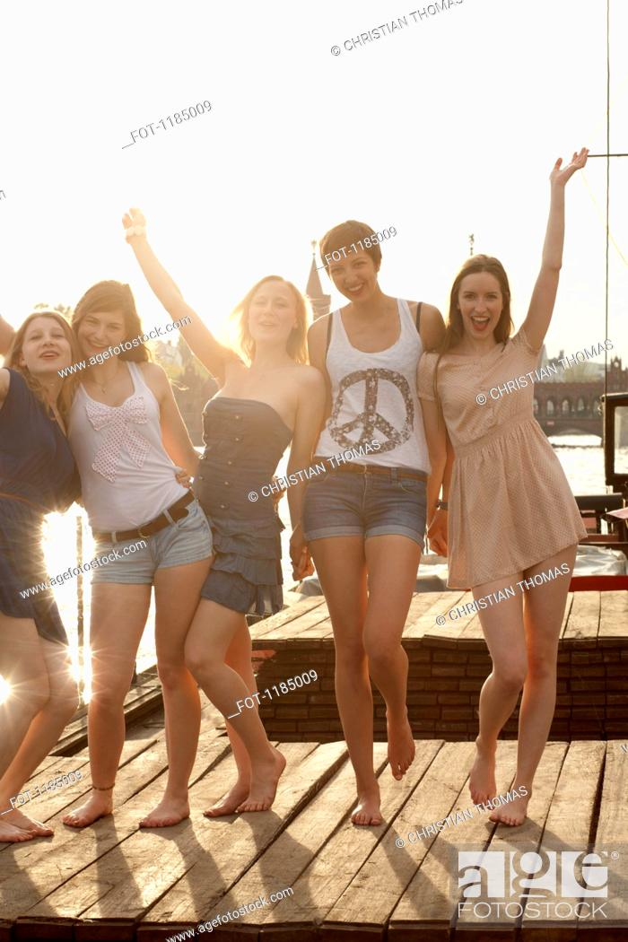 Stock Photo: Five young female friends celebrating on a jetty, Spree River, Berlin, Germany.