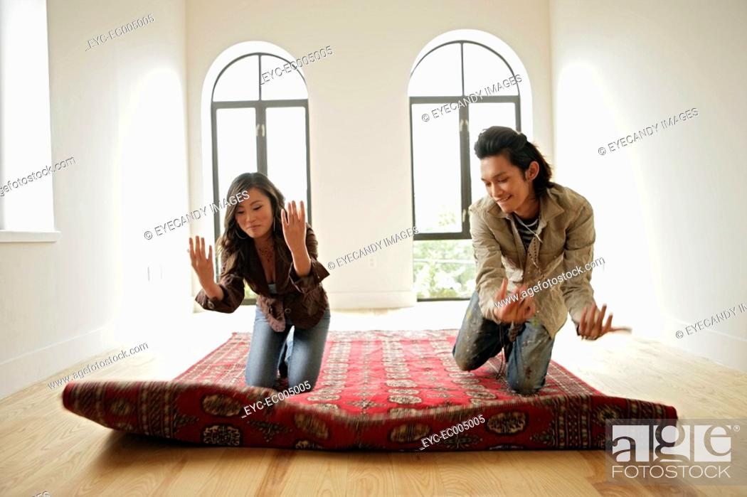 Stock Photo: Two people kneeling on carpet, front view.