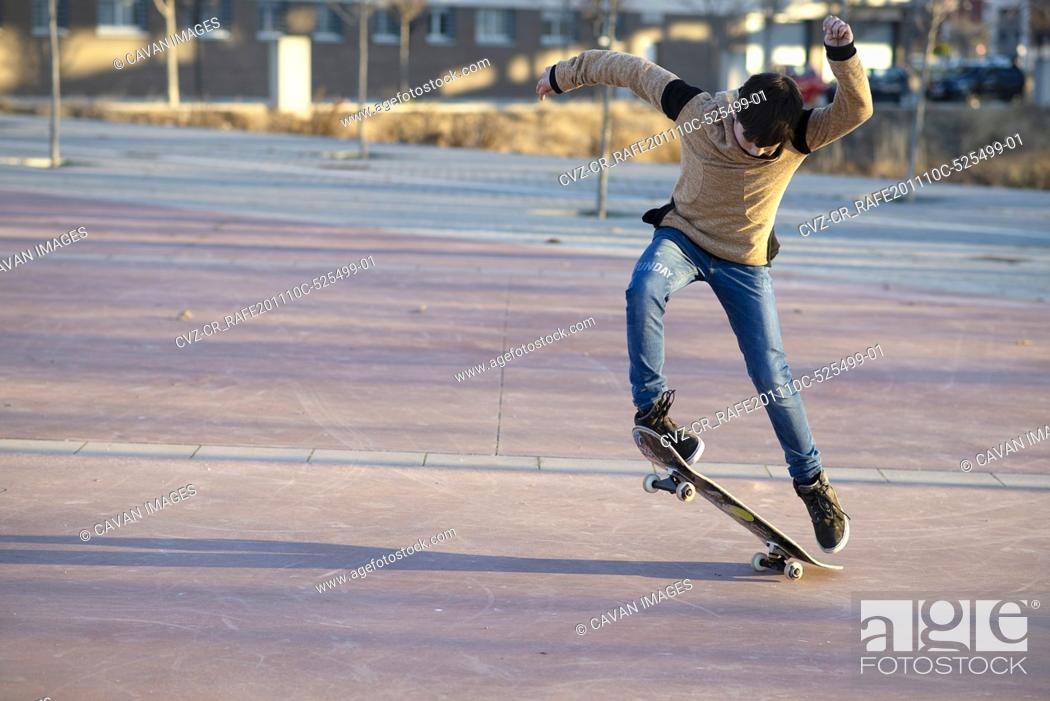 Stock Photo: Young Caucasian teen with red hut jumping on a skateboard in the city.