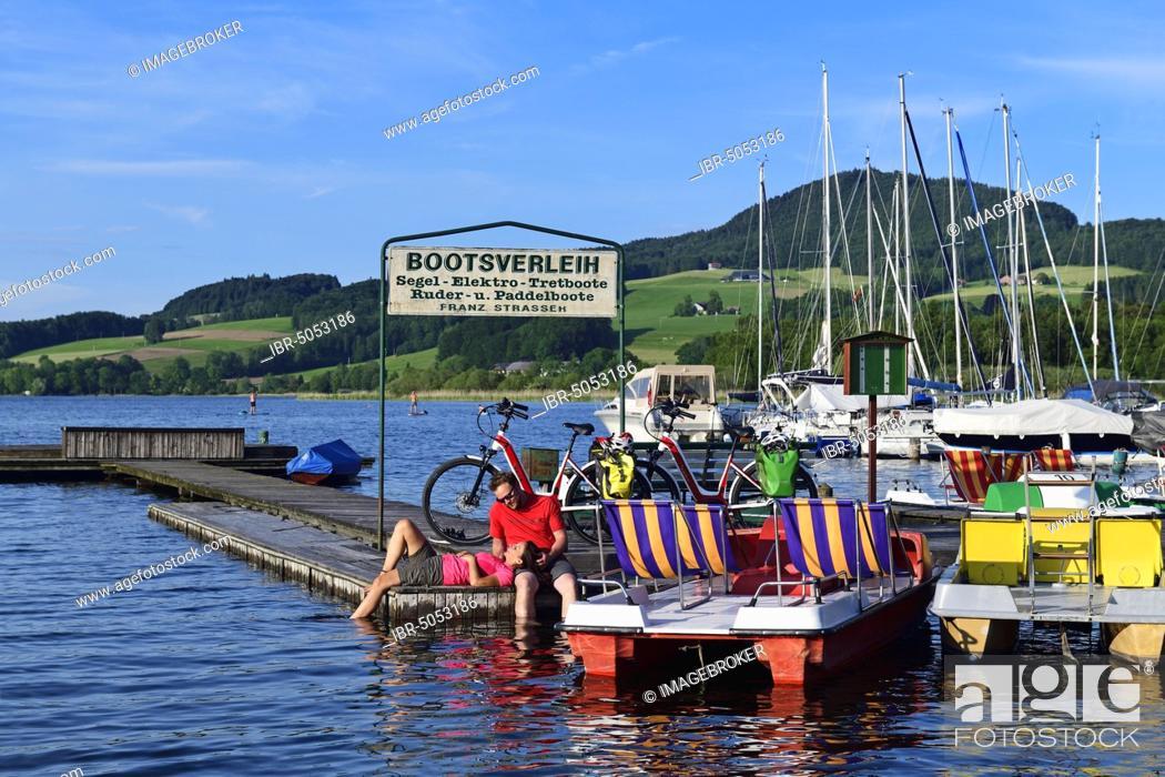 Stock Photo: Couple with electric bikes pauses on a landing stage at Lake Obertrumer See, Obertrum, Salzburger Seenland, Salzburger Land, Austria, Europe.
