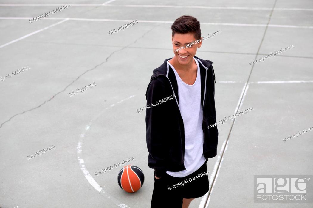 Stock Photo: Male teenage basketball player on basketball court, smiling.