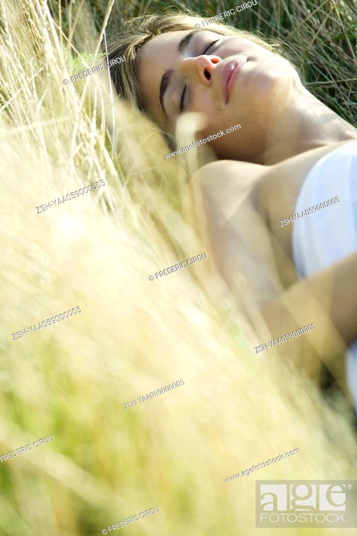 Stock Photo: Young woman lying in field with eyes closed, cropped view.