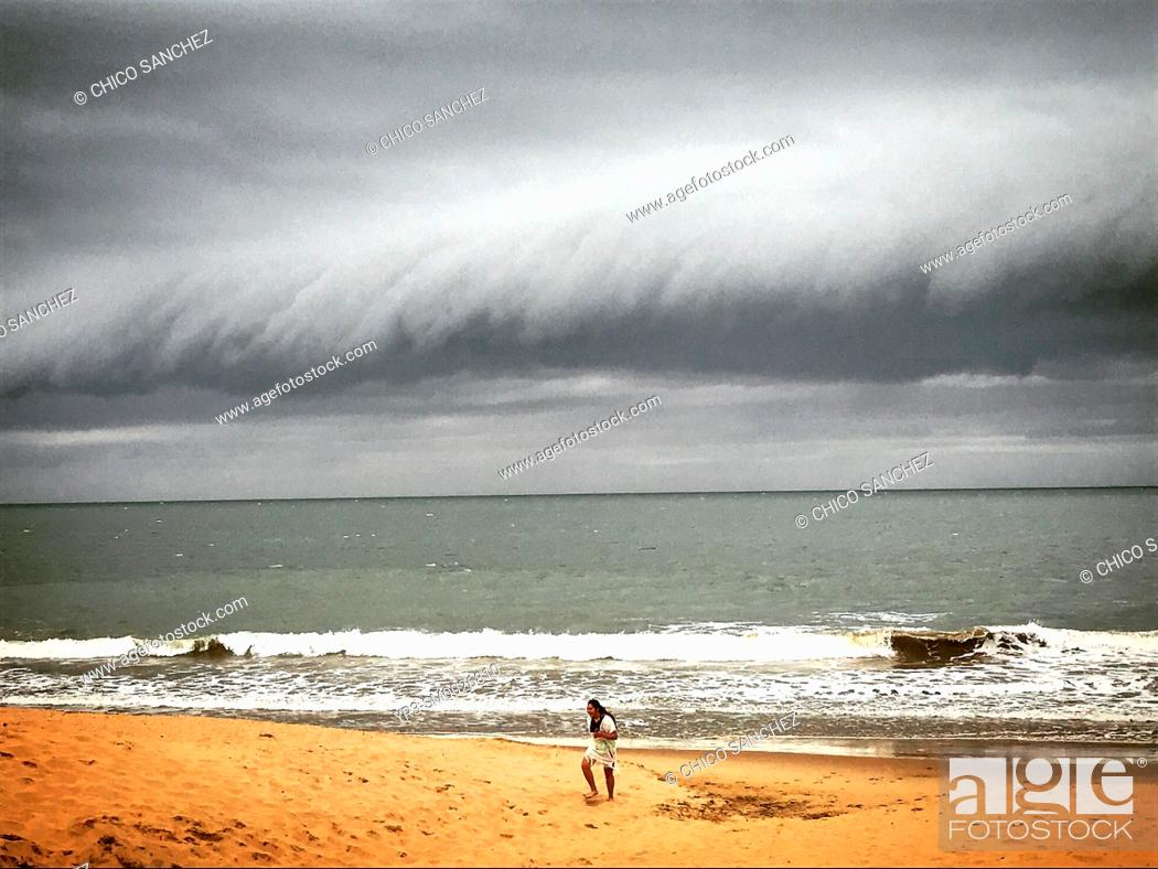 Stock Photo: A girl runs in the beach as a storm aproaches in the beach of Chipiona, Cadiz, Andalucia, Spain.