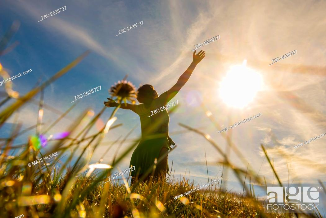 Stock Photo: Low angle view on a woman with raised arms and grass and sunshine in Grisons, Switzerland.