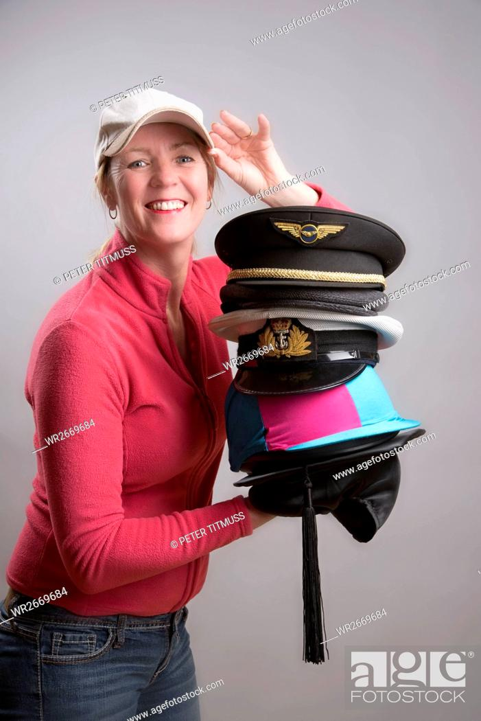 Stock Photo: Woman Holding A Selection Of Hats Business And Pleasure.