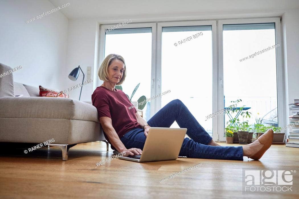 Stock Photo: Mature woman at home using laptop on the floor.