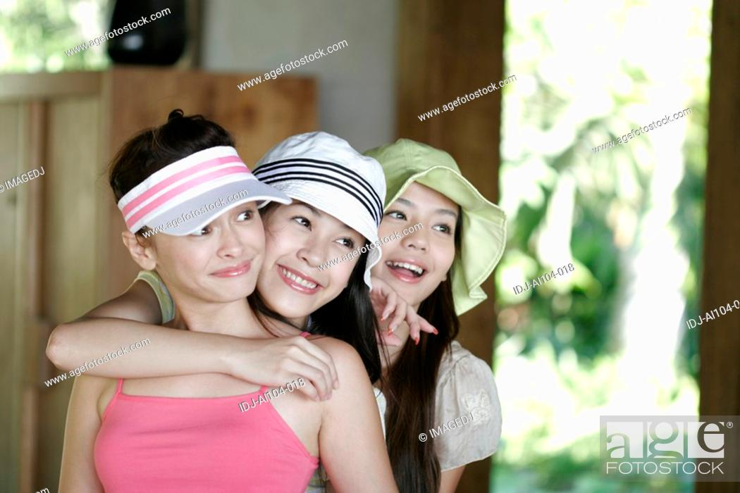Stock Photo: View of young women standing in row and smiling.