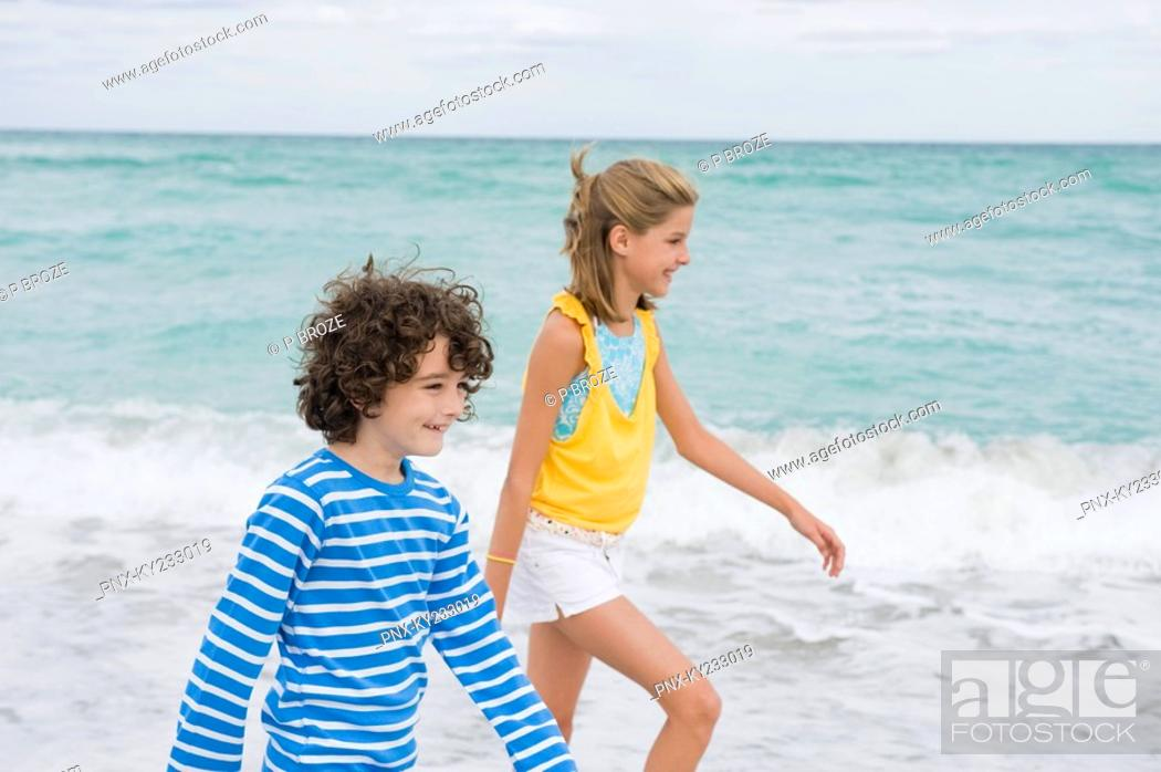 Stock Photo: Boy walking with a girl on the beach.