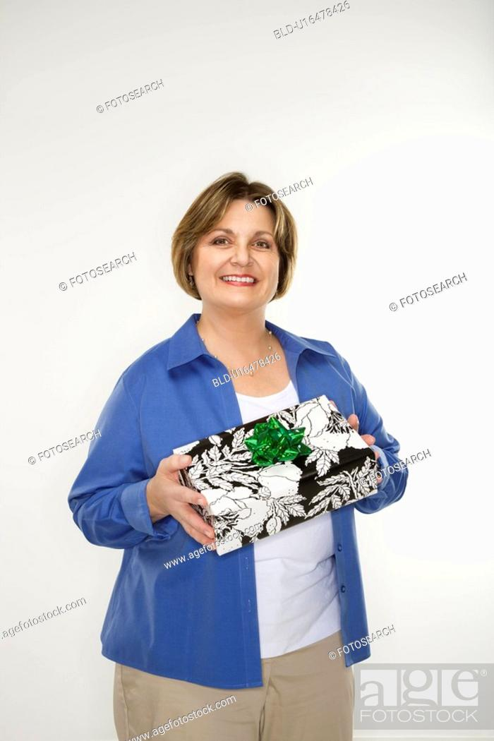 Stock Photo: Caucasian middle aged woman holding present and smiling at viewer.