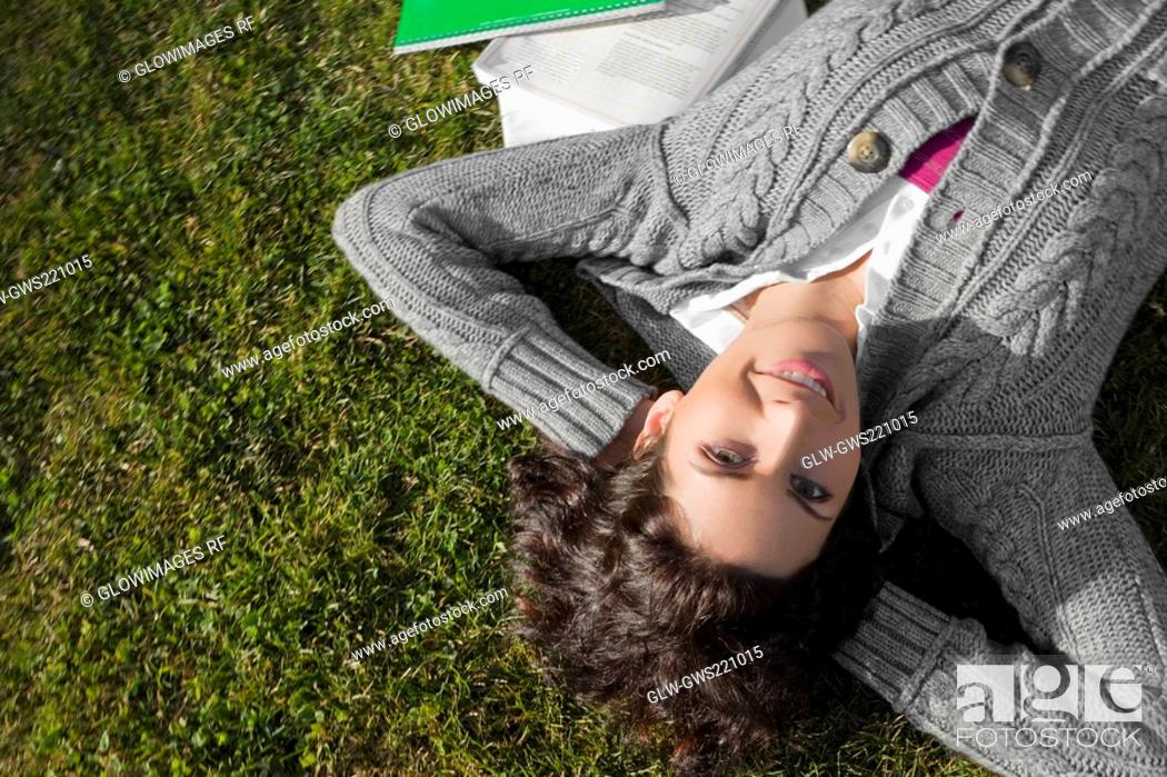 Stock Photo: Portrait of a young woman lying in a lawn.