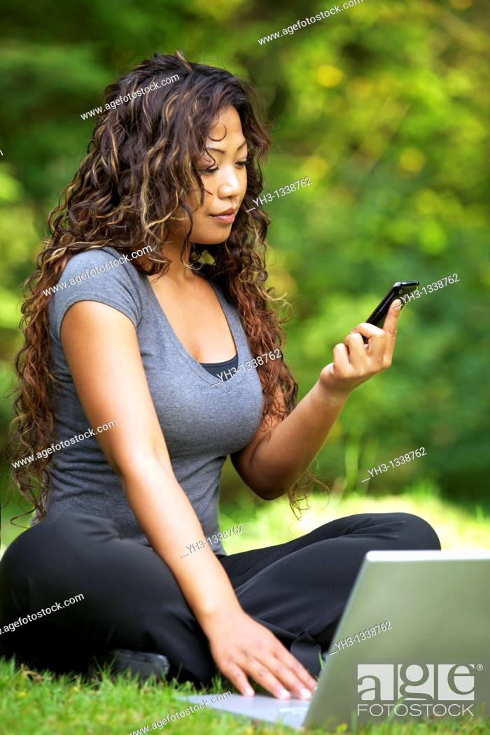 Stock Photo: A beautiful African American woman using laptop while holding a smartphone.