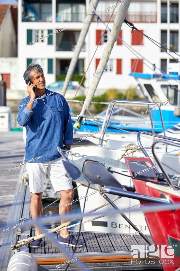 Stock Photo: Man in the harbor, talking on phone. Port De Plaisance Larraldenia, Ciboure, Aquitaine, Basque Country, France.
