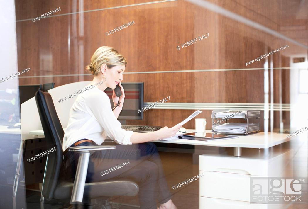 Stock Photo: Businesswoman talking on telephone at desk in office.