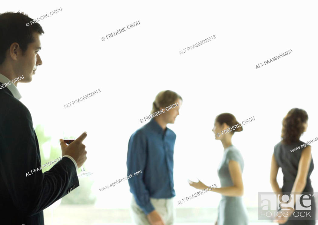Stock Photo: Man watching man and woman talk during cocktail party.
