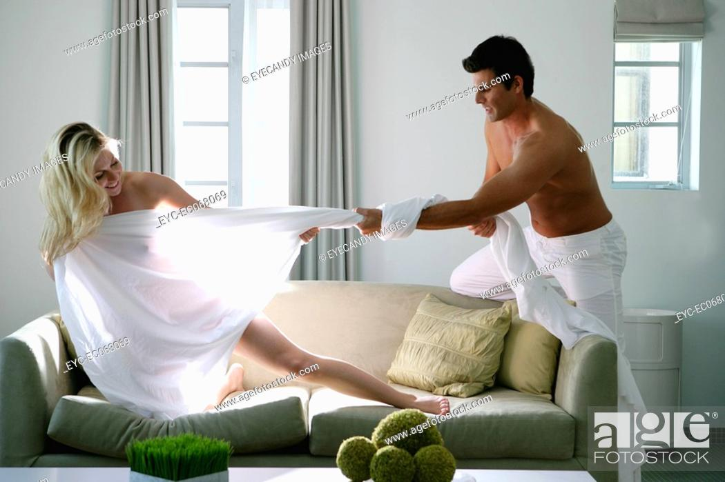 Stock Photo: Young man pulling sheet of nude woman.