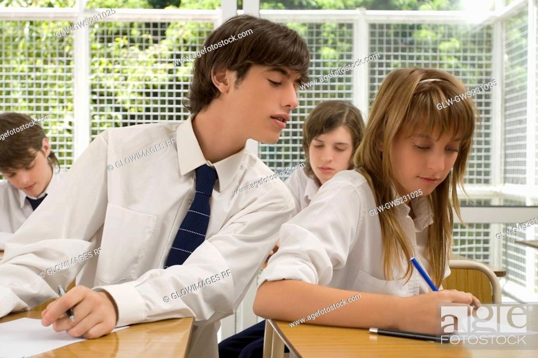Stock Photo: Young man peeping into a teenage girl's examination sheet.