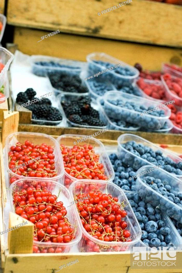 Stock Photo: Various types of berries in plastic punnets at a market.