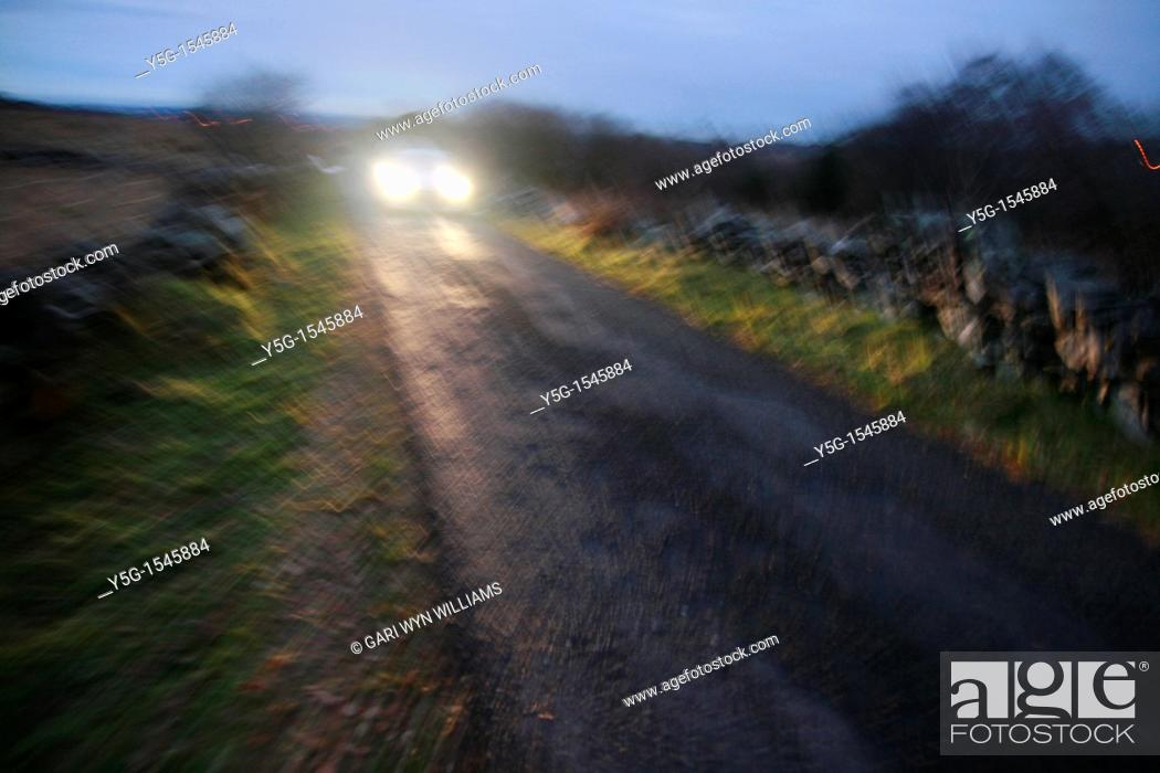 Stock Photo: one car on rural country lane at night.