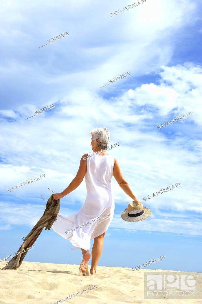 Photo de stock: Mature woman in a white suit enjoying an afternoon on the Islantilla beach, Huelva.