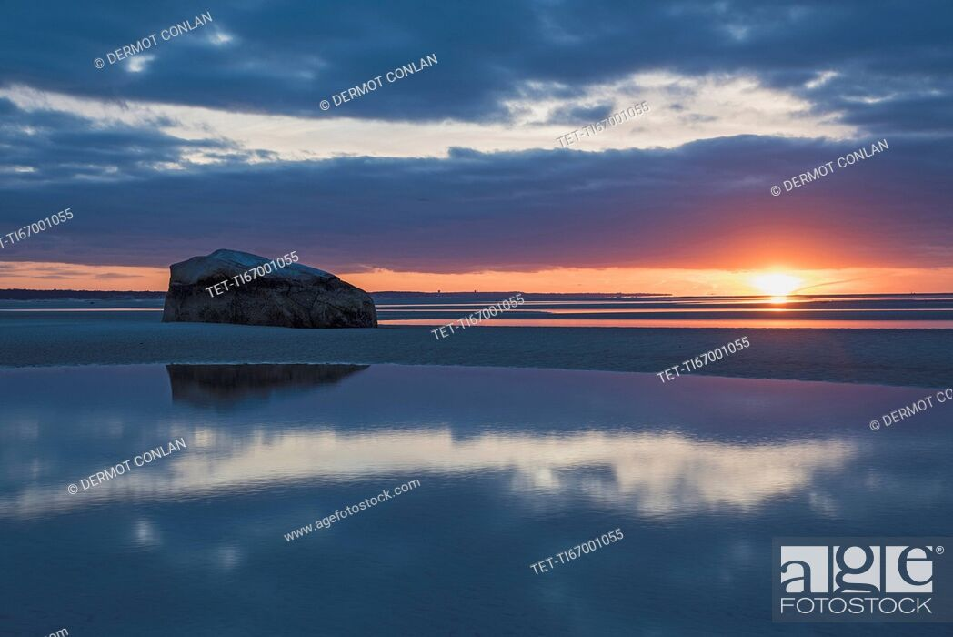 Imagen: USA, Massachusetts, Cape Cod, Orleans, Rock reflecting in sea at sunset.