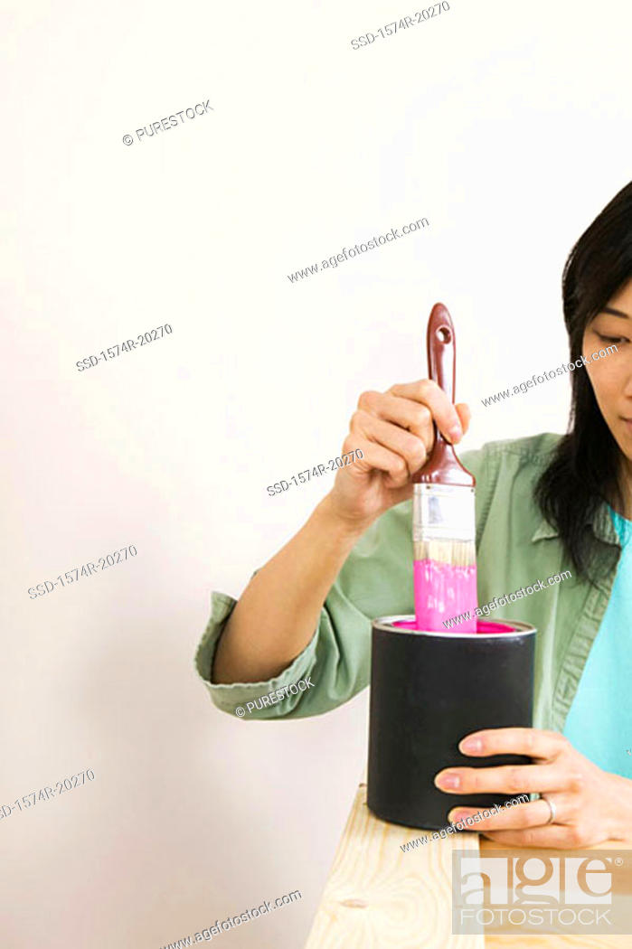 Stock Photo: Close-up of a young woman dipping a paintbrush into a paint can.