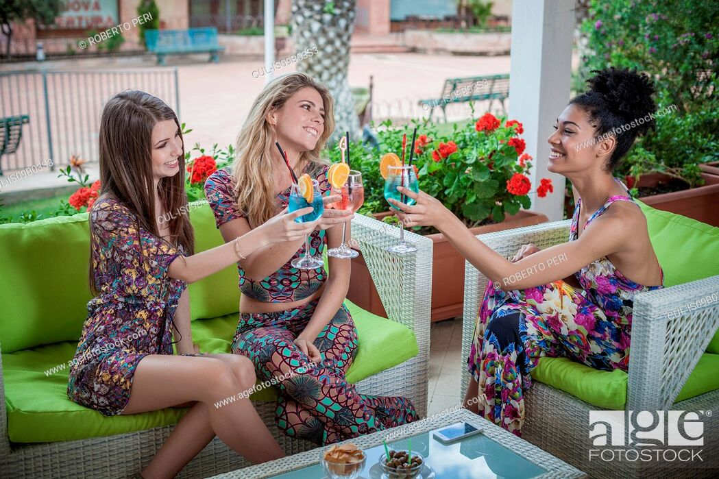 Stock Photo: Three young women relaxing on apartment patio raising a cocktail toast, Costa Rei, Sardinia, Italy.