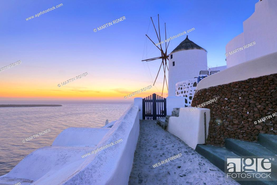 Stock Photo: Greece, View of Oia village with traditional Greek windmills in sunset at Santorini.