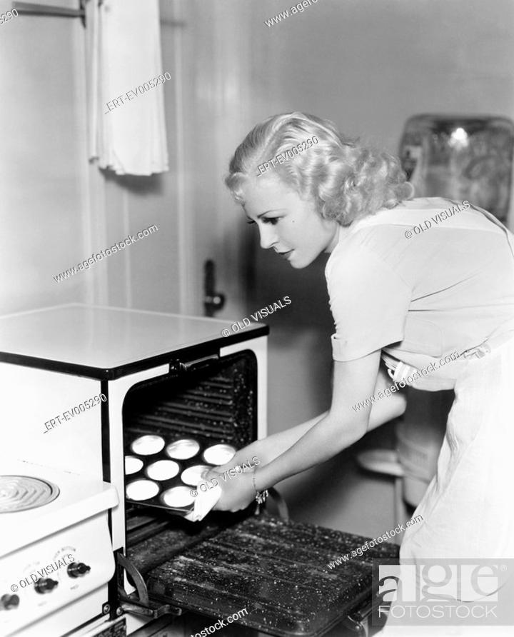 Stock Photo: Young woman taking cookies out of an oven All persons depicted are not longer living and no estate exists Supplier warranties that there will be no model.