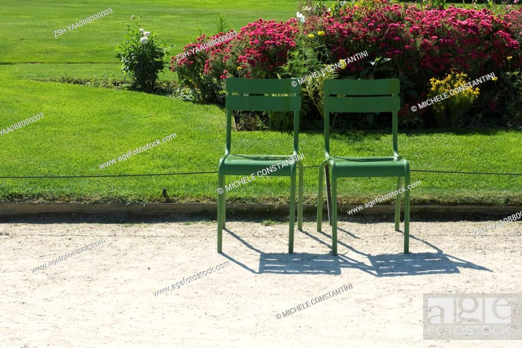 Stock Photo: France, Paris, metal chairs set side by side in park.