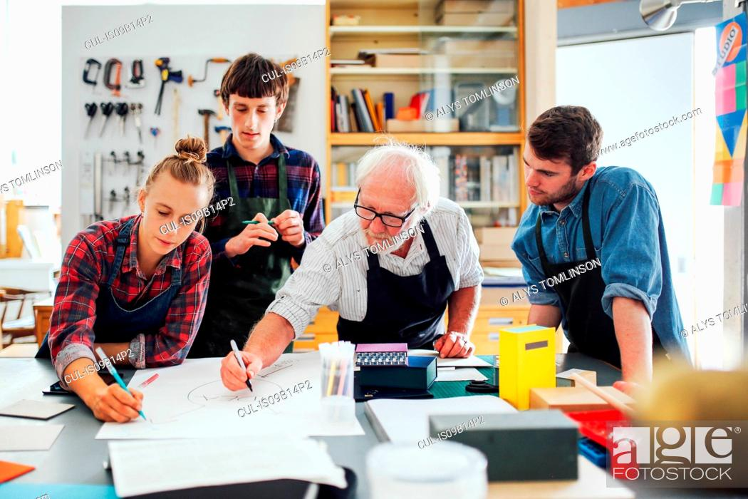 Stock Photo: Senior male craftsman brainstorming ideas with group of young men and women in book arts workshop.