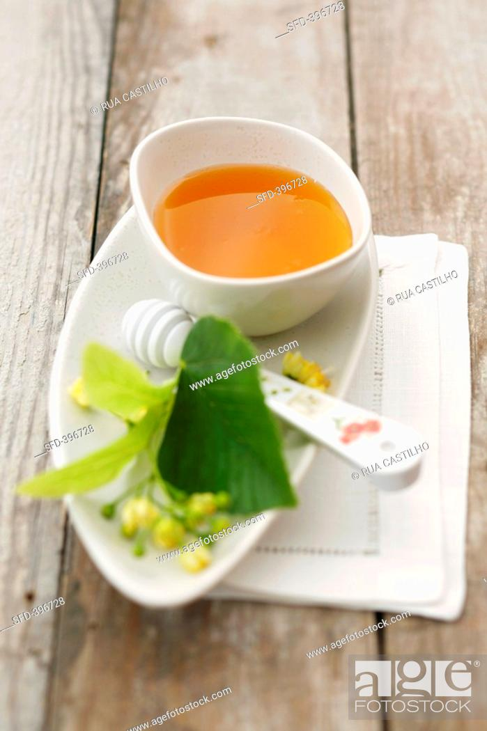 Stock Photo: Lime blossom honey in a small dish with lime blossom.