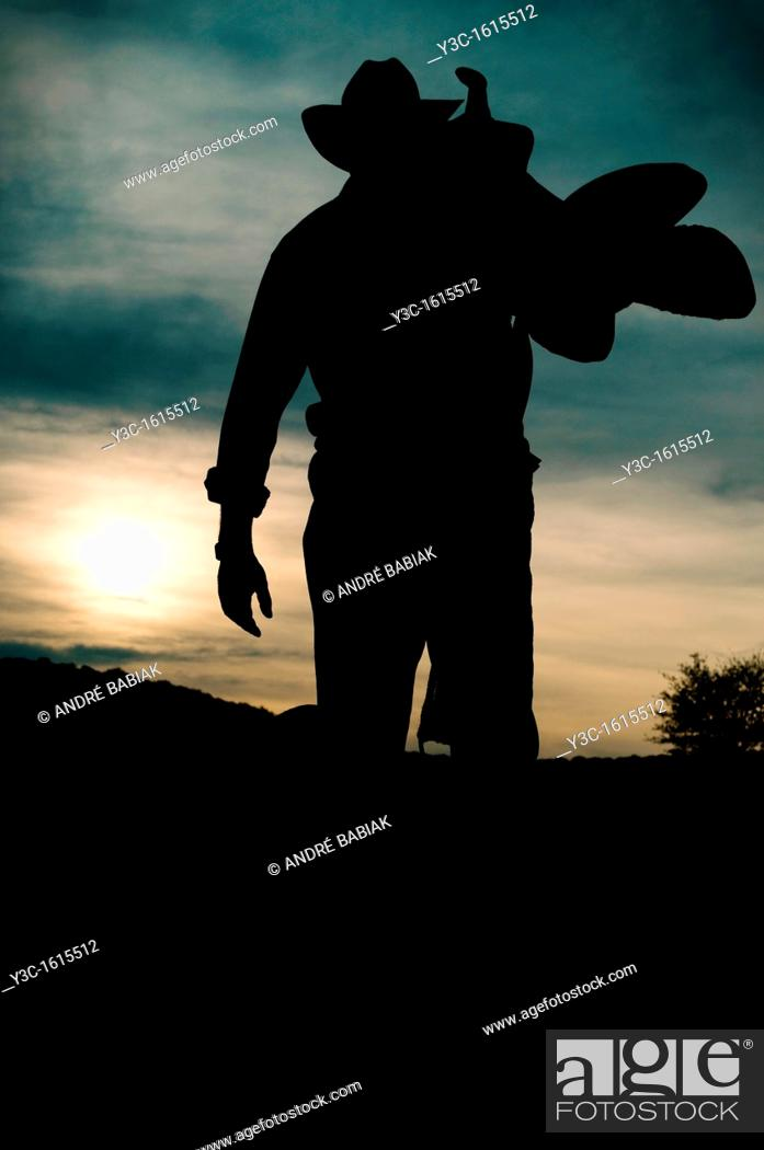 Stock Photo: Working man silhouette at sunset - Cowboy calling it a day.
