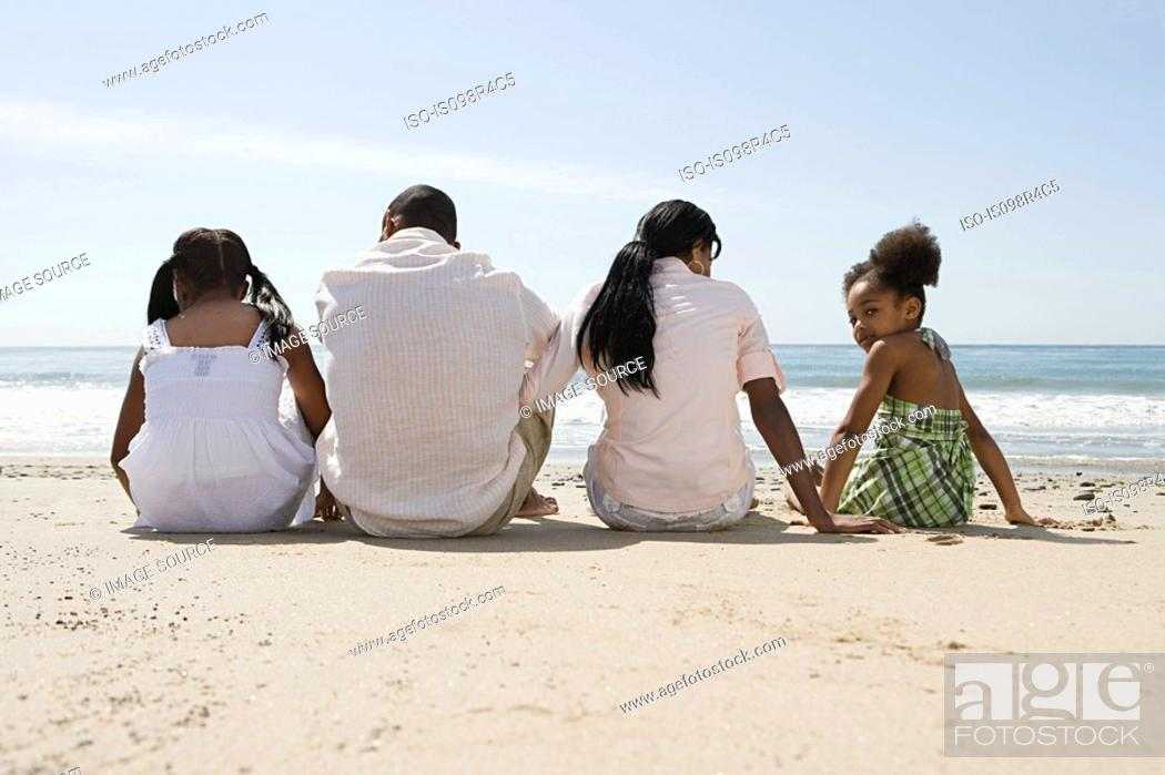 Stock Photo: African american family sitting on a beach.