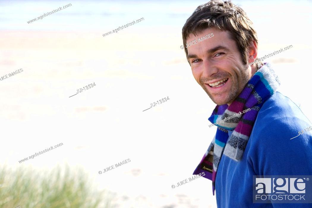 Stock Photo: Man standing on beach, smiling, portrait.