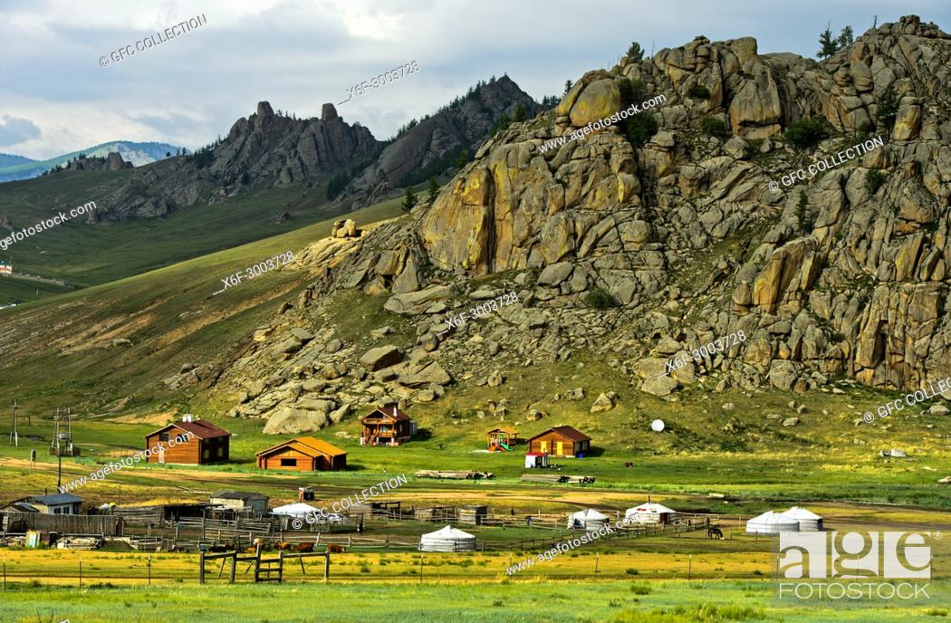 Photo de stock: Hamlet with yurts and blockhouses in front of a rocky peak in the Mongolian steppe, Gorkhi-Terelj National Park, Mongolia.