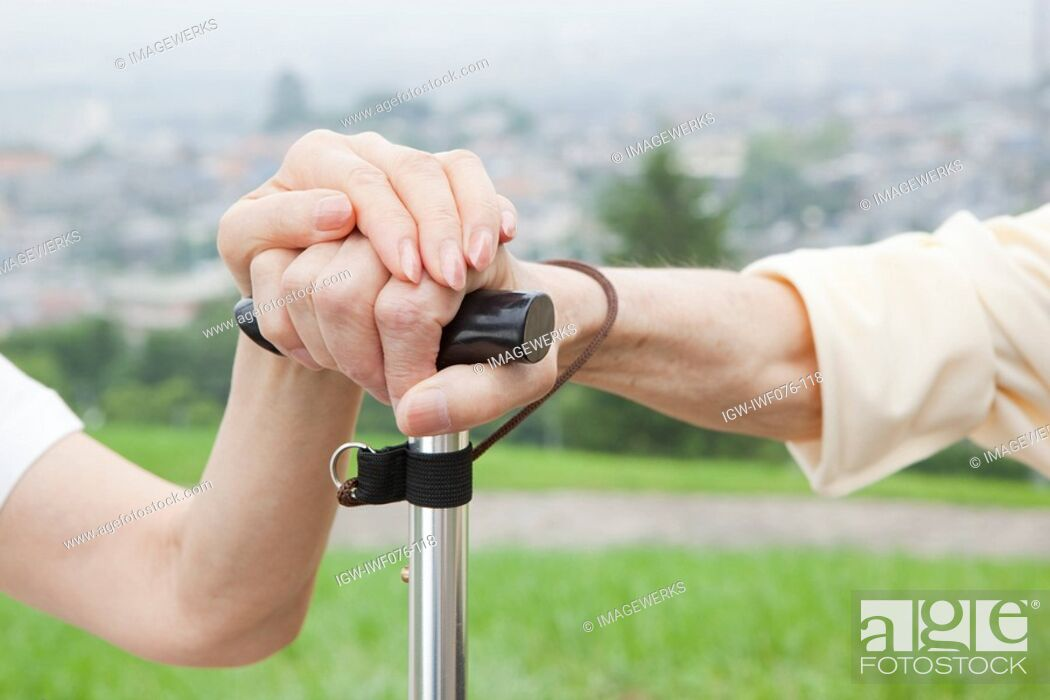 Stock Photo: Japan, Tokyo Prefecture, Senior couple's hand holding walking stick, close-up.