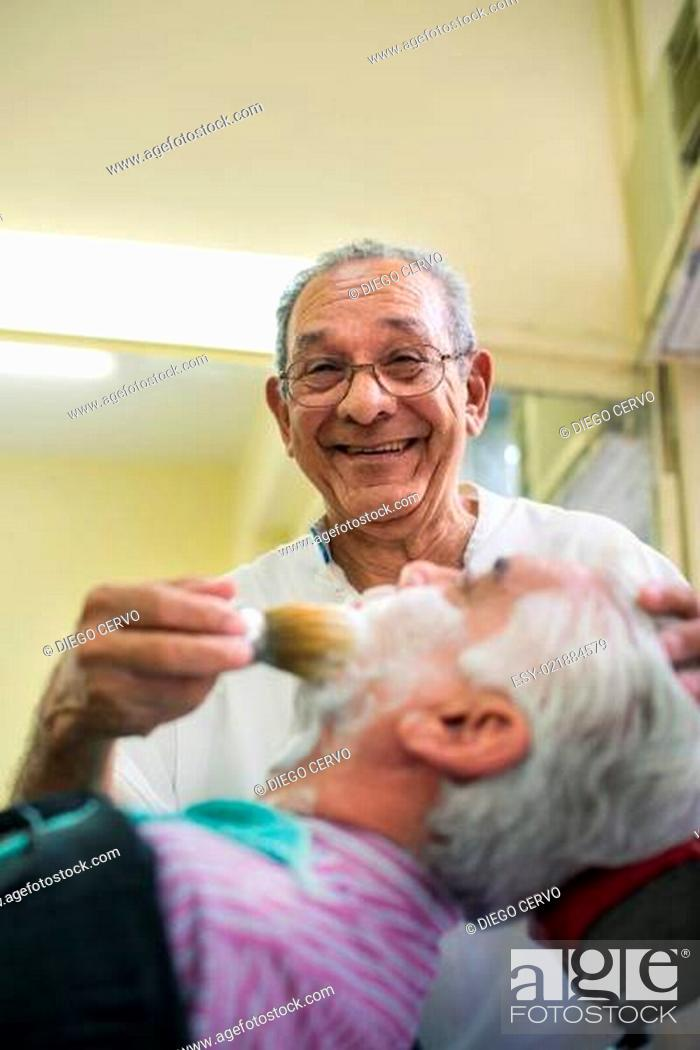 Stock Photo: Senior man at work as barber shaving customer.