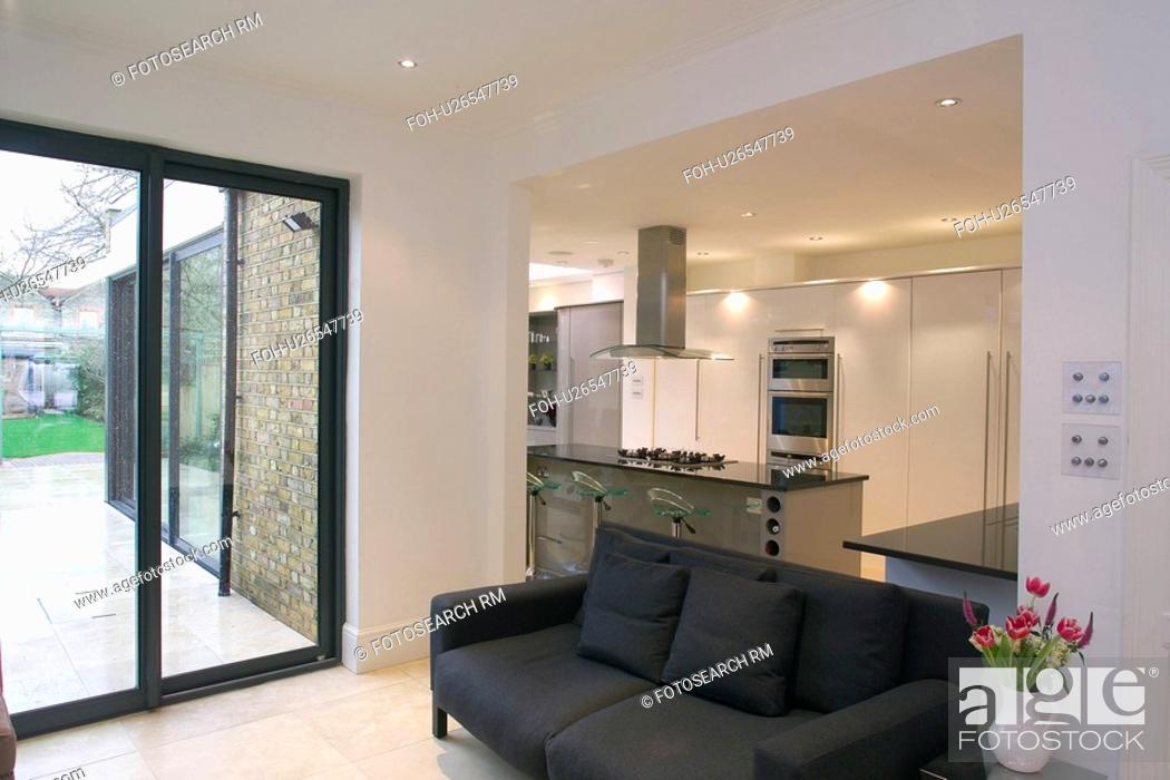 Glass Patio Doors And Black Sofa In Openplan Modern White Kitchen