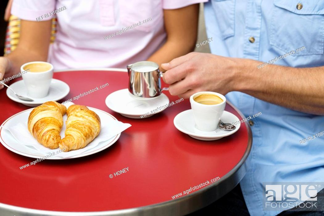 Stock Photo: Close up view of young couple sitting at table drinking coffee, Paris France.