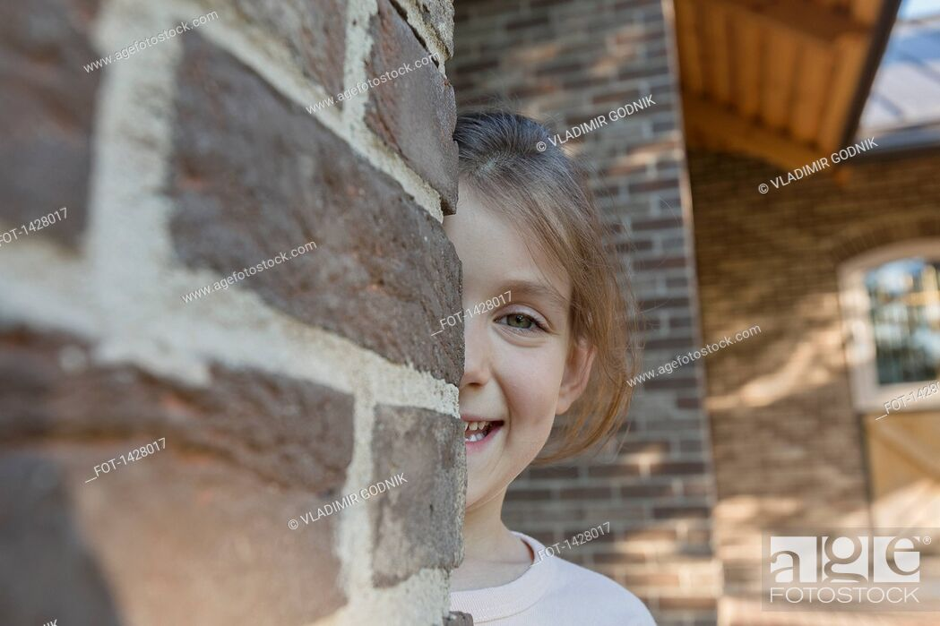 Stock Photo: Portrait of smiling girl hiding behind brick wall.