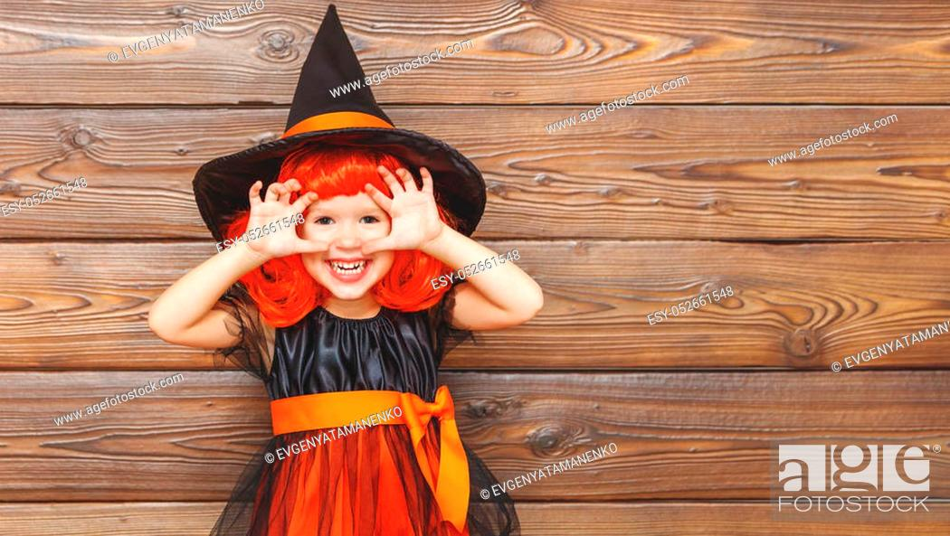 Stock Photo: funny child girl in witch costume for Halloween scares on a dark wooden background.