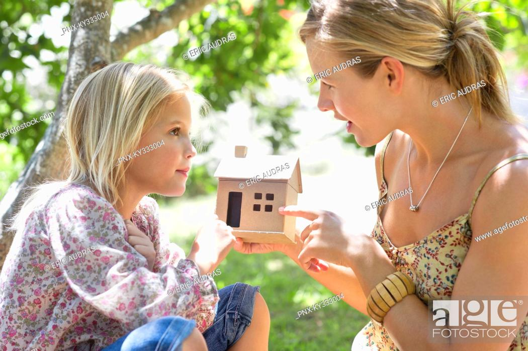Stock Photo: Little girl and her mother holding dollhouse outdoors.