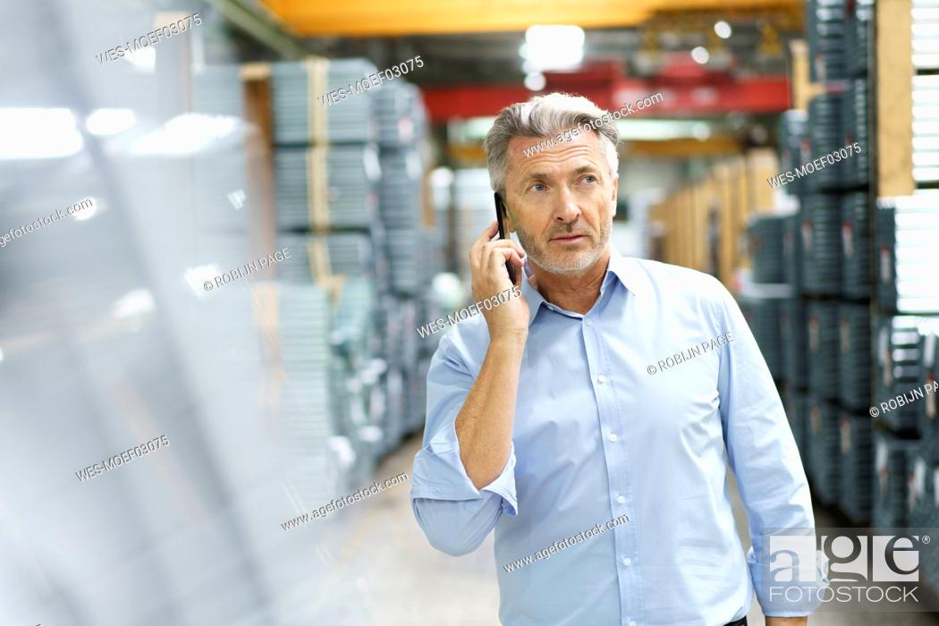 Stock Photo: Mature businessman on the phone in a factory.