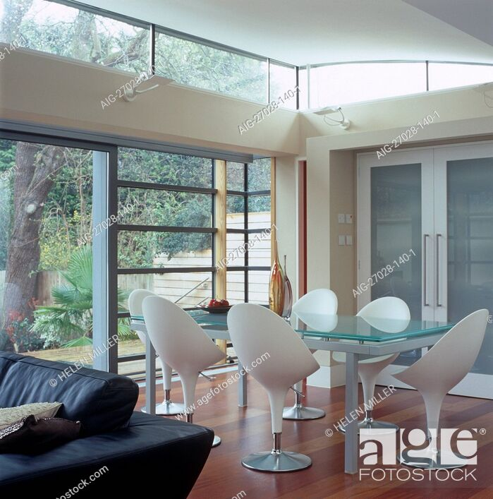 Stock Photo: Glass table and retro style chairs behind leather sofa in open plan room.