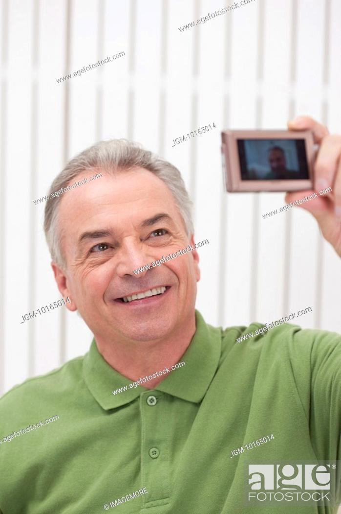 Stock Photo: Domestic Life, a senior man taking picture of himself and smiling.
