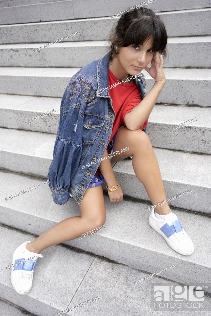 Imagen: Young woman sitting on steps.