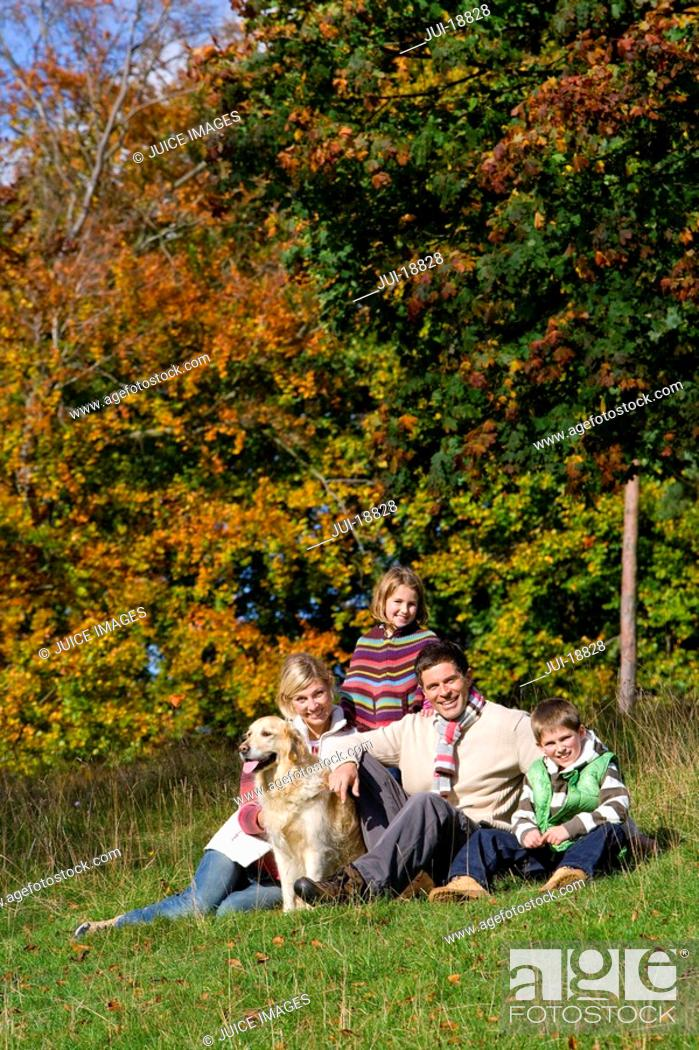 Stock Photo: Portrait of family and dog sitting in grass.