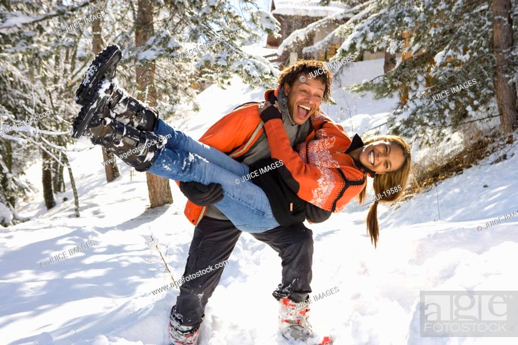 Stock Photo: Mixed race couple playing in snow, man holding woman.