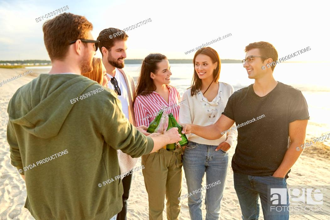 Stock Photo: friends toasting non alcoholic drinks on beach.