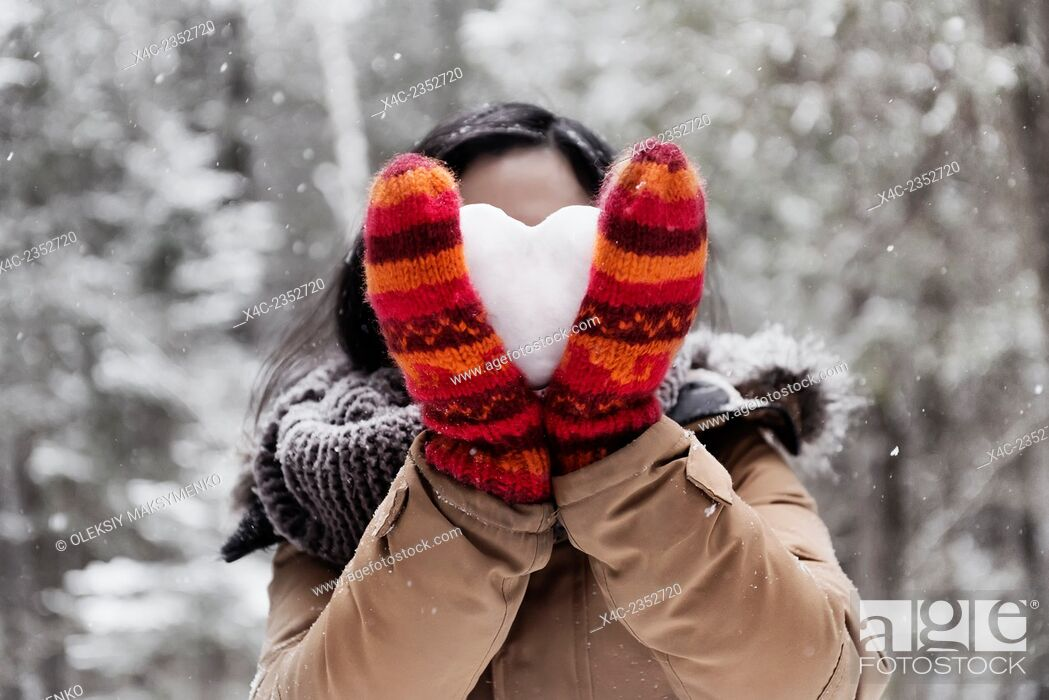 Stock Photo: Young woman in red mittens holding a heart made of snow in front of her face, romantic concept.